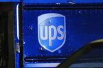 FILE- In this Dec. 5, 2019, file photo, bullet holes are seen around the UPS logo of a truck at the scene of a shooting that killed four people, including a UPS driver. The family of Frank Ordonez the UPS driver slain during the police shootout, have filed a lawsuit Wednesday, Sept. 16, 2020, against several law enforcement agencies. They say that officers acted negligently when they opened fire on two robbers who were holding him hostage inside his van. (AP Photo/Brynn Anderson, File)