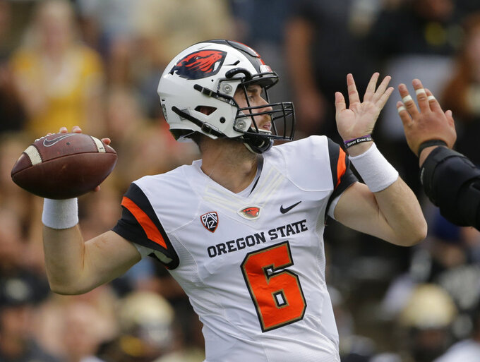 FILE - In this Oct. 27, 2018, file photo, Oregon State quarterback Jake Luton prepares to throw against Colorado during the second half of an NCAA college football game in Boulder, Colo. Saturday's game between USC and Oregon State will feature two contrasting teams. The Trojans are coming off a disheartening loss at home, while the Beavers had a statement-making win on the road. Luton, named the Pac-12 Offense Player of the Week, will start for Oregon State. (AP Photo/Jack Dempsey, File)