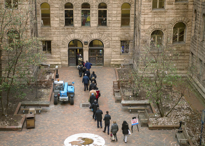 People arrive to the Allegheny County Courthouse prior to the start of the second day of the homicide trial of former East Pittsburgh police officer Michael Rosfeld, Wednesday, March 20, 2019, in Pittsburgh. Rosfeld, 30, faces a charge of criminal homicide for the June 2018 death of 17-year-old unarmed black high school student Antwon Rose II. (Nate Smallwood/Pittsburgh Tribune-Review via AP, Pool)
