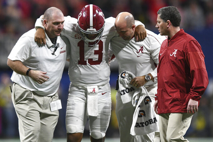 Alabama quarterback Tua Tagovailoa (13) comes off the field with an injury during an NCAA college football game against Georgia for the Southeastern Conference championship Saturday, Dec. 1, 2018, in Atlanta. (AJ Reynolds/Athens Banner-Herald via AP)