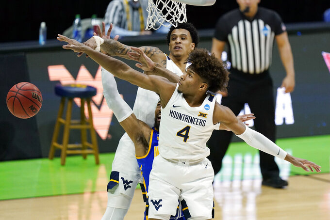 West Virginia's Miles McBride (4) reaches for a rebound against Morehead State during the first half of a college basketball game in the first round of the NCAA tournament at Lucas Oil Stadium Friday, March 19, 2021, in Indianapolis. (AP Photo/Mark Humphrey)