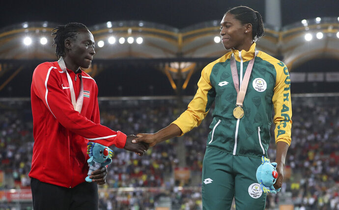 FILE - In this Friday, April 13, 2018 file photo, Women's 800m silver medal winner Kenya's Margaret Nyairera Wambui, left, shakes hands with gold medla winner South Africa's Caster Semenya on the podium at Carrara Stadium during the 2018 Commonwealth Games on the Gold Coast, Australia. Margaret Nyairera Wambui has criticized the IAAF's testosterone regulations and is refusing to take hormone-reducing medication. (AP Photo/Mark Schiefelbein, File)