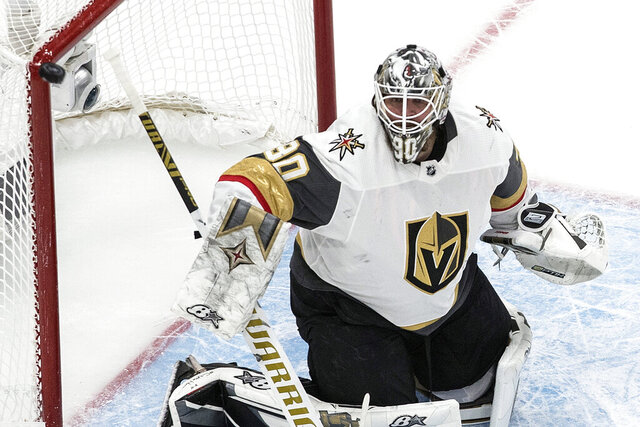 FILE - In this Sept. 10, 2020, file photo, the puck hits the post as Vegas Golden Knights goaltender Robin Lehner watches during the first period of Game 3 of the NHL hockey Western Conference final against the Dallas Stars in Edmonton, Alberta. The Golden Knights have re-signed Lehner to a $25 million, five-year contract that carries a $5 million annual salary cap hit. (Jason Franson/The Canadian Press via AP, File)