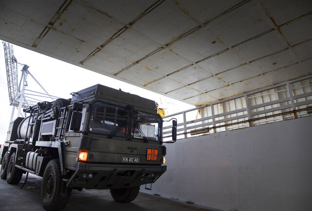 A military truck is unloaded from a British naval vessel, taking part in U.S.-led war games, at the Port of Antwerp in Antwerp, Belgium, Monday Feb. 3, 2020. The Defender-Europe 2020 exercises will involve approximately 20,000 American troops; the biggest deployment of U.S.-based soldiers to Europe in 25 years. (AP Photo/Virginia Mayo)