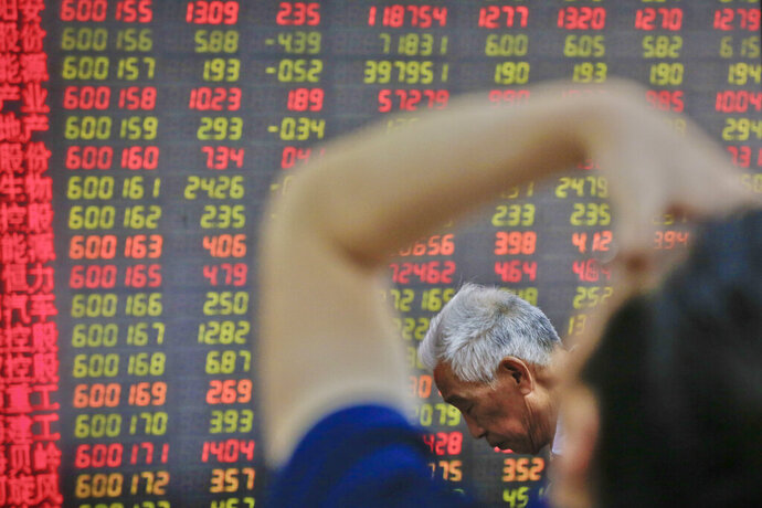 Chinese investors react as they monitor stock prices at a brokerage house in Beijing, Tuesday, May 14, 2019. Shares opened moderately lower in Asia on Tuesday after a dismal day on Wall Street as investors fled uncertainty over the China-U.S. trade standoff. (AP Photo/Andy Wong)