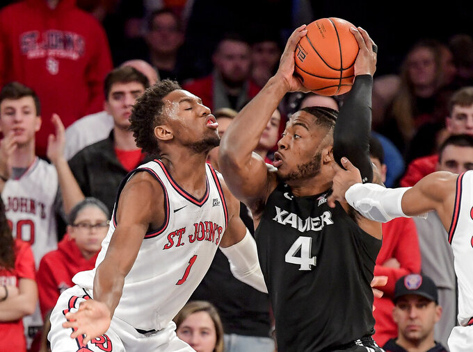 Xavier's Tyrique Jones (4) tries to get around the defense of St. John's Josh Roberts during an NCAA college basketball game in New York on Monday, Feb 17, 2020. (Steven Ryan/Newsday via AP)