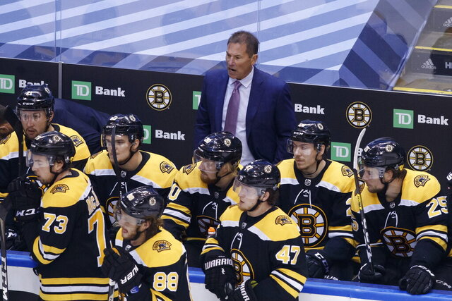 Boston Bruins head coach Bruce Cassidy, rear watches during the third period of an NHL hockey Stanley Cup playoff game against the Tampa Bay Lightning in Toronto, Saturday, Aug. 29, 2020. (Cole Burston/The Canadian Press via AP)