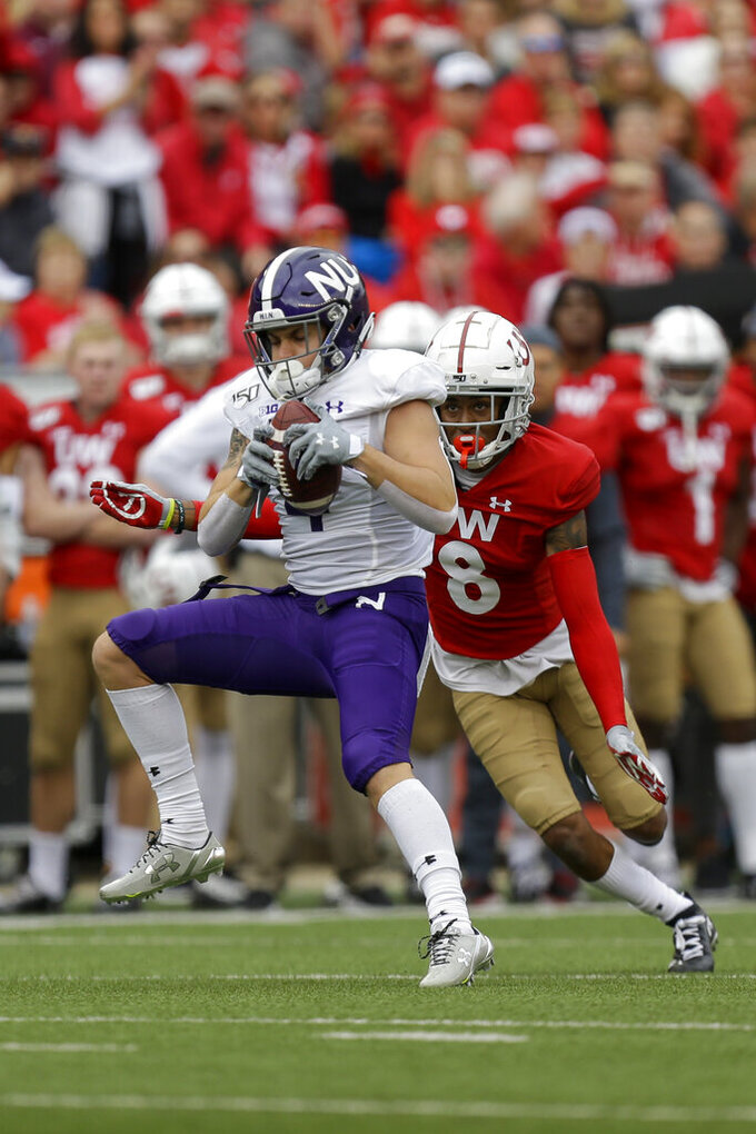 Northwestern wide receiver Berkeley Holman (4) makes a reception against Wisconsin cornerback Deron Harrell (8) during the first half of an NCAA college football game Saturday, Sept. 28, 2019, in Madison, Wis. (AP Photo/Andy Manis)