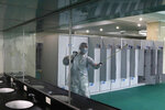 An employee wearing a protective gear disinfects to help curb the spread of the coronavirus at the Ryugyong Health Complex's public bath in Pyongyang, North Korea, Friday, July 31, 2020. (AP Photo/Cha Song Ho)