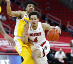 N.C. State's Jericole Hellems (4) drives by Pittsburgh's Ithiel Horton (0) during the first half of an NCAA college basketball game in Raleigh, N.C., Sunday, Feb. 28, 2021. (Ethan Hyman/The News & Observer via AP)