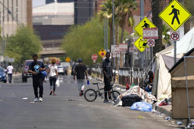 Pedestrians walk along the street next to a homeless encampment as temperatures continue to soar past 115-degrees Thursday, June 17, 2021, in Phoenix. (AP Photo/Ross D. Franklin)