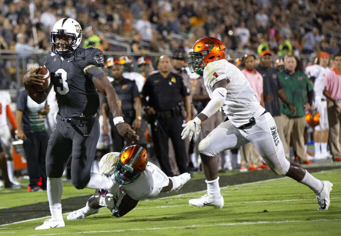 Central Florida quarterback Brandon Wimbush (3) breaks a tackle by Florida A&M defensive back Markquese Bell and safety Terry Jefferson (1) during the first half of an NCAA college football game Thursday, Aug. 29, 2019, in Orlando, Fla. (AP Photo/Willie J. Allen Jr.)