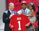 FILE - In this April 25, 2013, file photo, Eric Reid, from LSU, holds up his daughter next to NFL commissioner Roger Goodell after being selected 18th overall by the San Francisco 49ers in the first round of the NFL football draft, in New York. Colin Kaepernick and Eric Reid have reached settlements on their collusion lawsuits against the NFL, the league said Friday, Feb. 19, 2019. (AP Photo/Greg Payan, File)