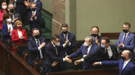 Poland's members of government with Prime Minister Mateusz Morawiecki, center, react after voting – some in parliament, some remotely – in Warsaw, Poland, on Tuesday, May 4, 2021. Polish lawmakers have voted to approve the nation's spending plan for the 58 billion euros ($70 billion) it expects to receive from the European Union's pandemic recovery plan. (AP Photo/Czarek Sokolowski)