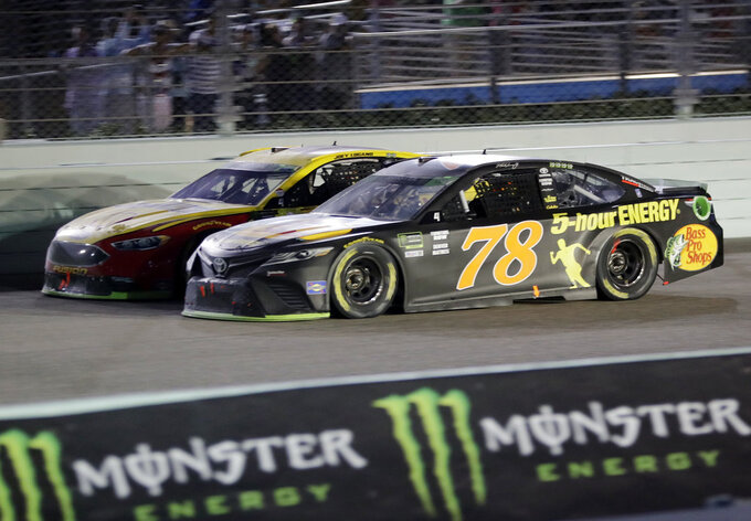 Joey Logano, left, and Martin Truex Jr. (78) drive on the track during the NASCAR Cup Series Championship auto race at the Homestead-Miami Speedway, Sunday, Nov. 18, 2018, in Homestead, Fla. (AP Photo/Lynne Sladky)