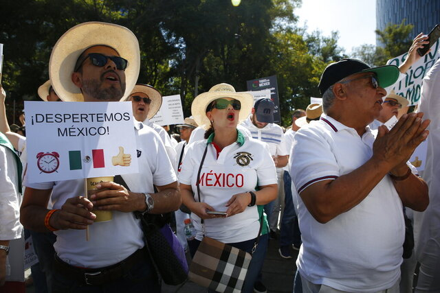 A man holds a sign the reads in Spanish