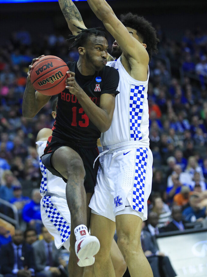 Houston's DeJon Jarreau (13) passes around Kentucky's Nick Richards during the second half of a men's NCAA tournament college basketball Midwest Regional semifinal game Friday, March 29, 2019, in Kansas City, Mo. (AP Photo/Orlin Wagner)