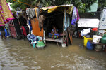 A woman sits inside her hut at a flooded street in Chennai, India, Wednesday, Nov.25, 2020. India's southern state of Tamil Nadu is bracing for Cyclone Nivar that is expected to make landfall on Wednesday. The state authorities have issued an alert and asked people living in low-lying and flood-prone areas to move to safer places. (AP Photo/R. Parthibhan)