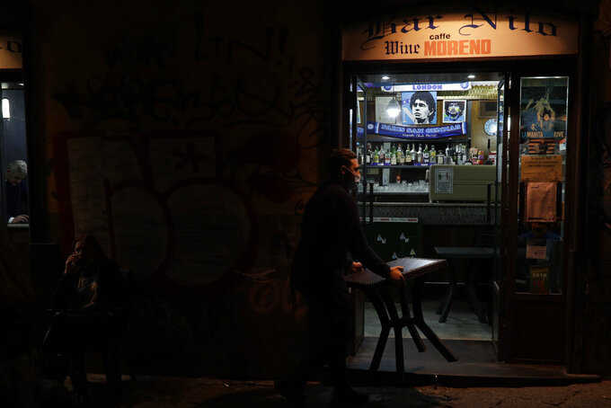A bartender carries a table inside as he is closing the Nilo Bar in Naples, in the region of Campania, Italy, Friday, Nov. 13, 2020. The regions of Campania and Tuscany were designated red zone on Friday, signaling the dire condition of a hospitals struggling with a surge of new admissions. (AP Photo/Gregorio Borgia)