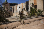 File - In this Thursday, Sept. 22, 2016 file photo, a fighter of the Libyan forces, affiliated to the Tripoli government, runs for cover while fighting against Islamic State positions in Sirte, Libya, The United Nations said , that the two sides in Libyan military talks had reached a