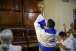 Father Harvey Padilla exposes the consecrated host to one of the barricaded doors of the San Juan Bautista Church after supporters of President Daniel Ortega attempted to enter the church by force, in Masaya, Nicaragua, Thursday, Nov. 21, 2019. The pro-Ortega group disrupted a mass in support of a group of mothers who are engaged in a hunger strike at the San Miguel Church in Masaya, to demand the release of their sons and daughters who are imprisoned by the Ortega government. Father Padilla and his parishioners are now barricaded in the church and surrounded by the police and pro-Ortega militants. (AP Photo/Alfredo Zuniga)