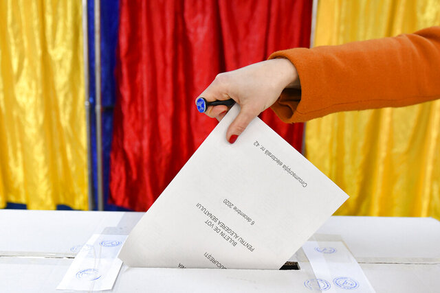 A woman casts her vote in Bucharest, Romania, Sunday, Dec. 6, 2020. Voting started in Romania's legislative election expected to restore some measure of stability after five years of political and social turbulence with more than 18 million Romanians registered to vote for a new legislative body. (AP Photo/Andreea Alexandru)