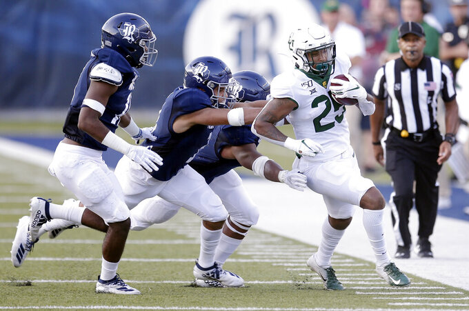 Rice linebacker Treshawn Chamberlain, safety Naeem Smith and defensive lineman Ikenna Enechukwu, from left, chase Baylor running back Trestan Ebner during the first half of an NCAA college football game Saturday, Sept. 21, 2019, in Houston. (AP Photo/Michael Wyke)