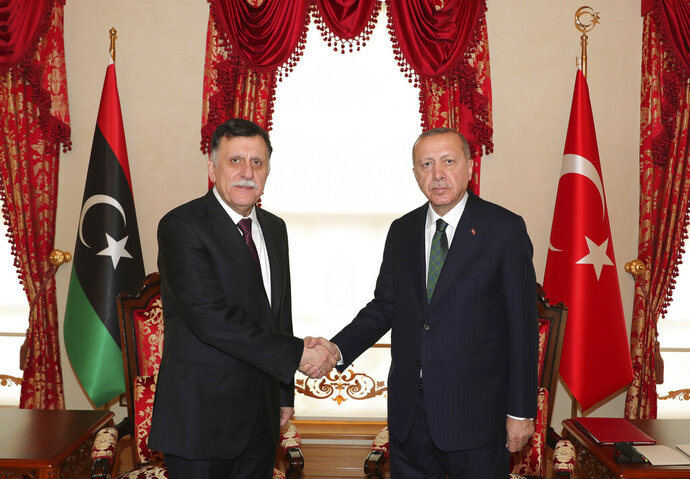 "FILE - In this Jan. 12, 2020 file photo, Turkey's President Recep Tayyip Erdogan, right, shakes hands with Fayez Sarraj, the head of Libya's internationally-recognized government, prior to their meeting in Istanbul. Two Libyan militia commanders and a Syrian war monitor group say Turkey is deploying Syrian extremists to fight in Libya's civil war. These extremists are affiliated with groups like al-Qaida and the Islamic State. They're fighting as mercenaries on behalf of the United Nations-supported government in Libya. The Libyan sources told The Associated Press that Turkey has airlifted more than 2,500 foreign fighters into Tripoli, and that ""dozens"" are extremist-affiliated. (Turkish Presidency via AP, Pool, File)"