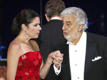 "FILE - In this file photo taken on Aug. 28, 2019, Opera star Placido Domingo holds the hand of Ana Maria Martinez at the end of a concert in Szeged, Hungary. The 78-year-old singer who rose to stardom as a tenor has been confirmed to sing the baritone title role in ""Nabucco"" at the Zurich Opera House this Sunday. It will be his first time performing since stepping down Oct. 2 as general director of the Los Angeles Opera and withdrawing from future performances at the company. (AP Photo/Laszlo Balogh)"