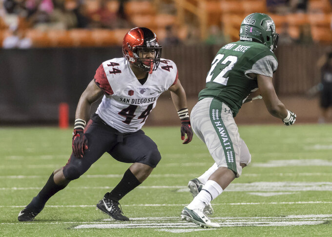 FILE - In this Saturday, Oct. 28, 2017 file photo, San Diego State linebacker Kyahva Tezino (44) attempts to chase down Hawaii running back Diocemy Saint Juste (22) in the fourth quarter of an NCAA college football game in Honolulu. Ohio goes for its third win in a row, and sixth in seven games when the Bobcats play San Diego State in the Frisco Bowl in suburban Dallas, on Wednesday, Dec. 19, 2018. (AP Photo/Eugene Tanner, File)