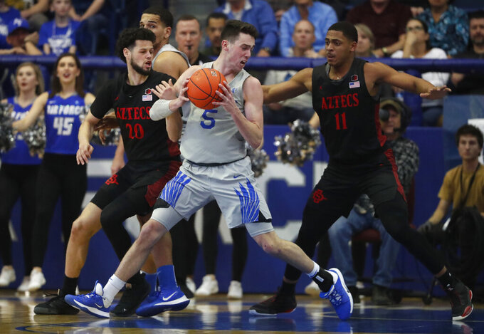 Air Force guard Chris Joyce, front, looks to drive to the basket as San Diego State guard Jordan Schakel, back left, and forward Matt Mitchell defend in the second half of an NCAA college basketball game Saturday, Feb. 8, 2020, at Air Force Academy, Colo. (AP Photo/David Zalubowski)