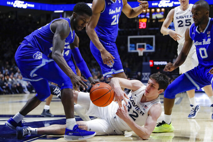 Xavier's Zach Freemantle (32) and Seton Hall's Myles Cale, left, scramble for a loose ball during the first half of an NCAA college basketball game, Wednesday, Jan. 8, 2020, in Cincinnati. (AP Photo/John Minchillo)