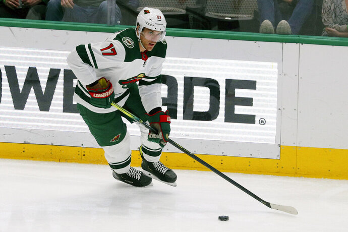 FILE - In this Feb. 7, 2020, file photo, Minnesota Wild left wing Marcus Foligno (17) moves the puck during an NHL hockey game against the Dallas Stars in Dallas. The Wild have signed Foligno to a three-year, $9.3 million contract extension, the team announced.  (AP Photo/Richard W. Rodriguez, File)