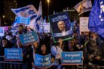Supporters of the Israeli Prime Minister Benjamin Netanyahu rally outside Israel's parliament in Jerusalem, Wednesday, Dec. 11, 2019. The Israeli parliament began voting to dissolve itself on Wednesday and pave the path to an unprecedented third election within a year. Hebrew in posters reads: