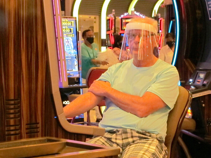A gambler wears a face shield while playing a slot machine at the Hard Rock casino in Atlantic City N.J. on July 2, 2020, the first day it was allowed to reopen during the coronavirus pandemic. Figures released on April 9, 2021 show Atlantic City's nine casinos collectively saw their gross operating profits decline by more than 80% in 2020.(AP Photo/Wayne Parry)