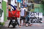 """A delivery man hands over food order to another at a fence set up block traffic in Vung Tau, Vietnam, Monday, Sept. 13, 2021. The sign at right reads """"No non-resident"""". The roadblocks and barricades make the streets of this southern Vietnamese city look like they did during the war that ended almost 50 years ago. But this time, the battle is being fought against the rampaging coronavirus.(AP Photo/Hau Dinh)"""