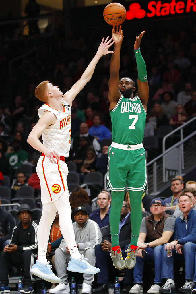 Boston Celtics guard Jaylen Brown (7) shoots as Atlanta Hawks guard Kevin Huerter (3) defends in the first half of an NBA basketball game on Monday, Feb. 3, 2020, in Atlanta. (AP Photo/Todd Kirkland)