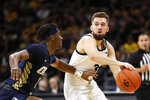 Iowa guard Jordan Bohannon, front right, passes around Oral Roberts guard Deondre Burns, left, during the first half of an NCAA college basketball game, Friday, Nov. 15, 2019, in Iowa City, Iowa. (AP Photo/Charlie Neibergall)