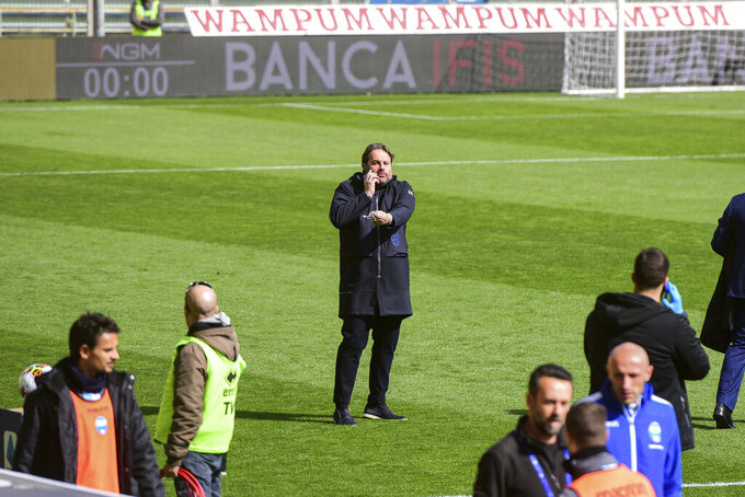 Parma's Sport's manager Daniele Faggiano, center, speaks on a phone moments before a Serie A soccer match between Parma and Spal was scheduled to be played, in Parma, northern Italy, Sunday, March 8, 2020. Parma and Spal players were ready to enter the field at Ennio Tardini stadium in Parma when they received the news that Italy's sports minister Vincenzo Spadafora said that the country's football federation should consider suspending the games. (Piero Cruciatti/LaPresse via AP)