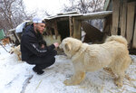 FILE - In this Feb. 23, 2018, file photo, American freestyle skier Gus Kenworthy plays with a dog at a dog meat farm in Siheung, South Korea. These days, freestyle skier Gus Kenworthy is one tough act to follow. His talents have him starring in a variety of roles both on and off the slopes. He's an actor (recently appearing in