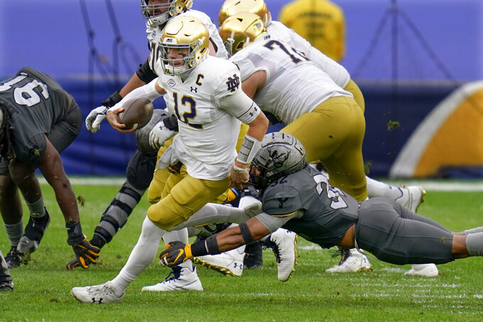 Notre Dame quarterback Ian Book (12) scrambles away from Pittsburgh linebacker SirVocea Dennis (32) for a first down during the first half of an NCAA college football game, Saturday, Oct. 24, 2020, in Pittsburgh. (AP Photo/Keith Srakocic)