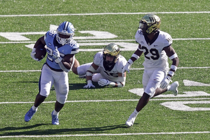 North Carolina running back Javonte Williams (25) runs while Wake Forest defensive back Caelen Carson (29) chases during the first half of an NCAA college football game in Chapel Hill, N.C., Saturday, Nov. 14, 2020. (AP Photo/Gerry Broome)