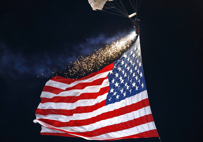 A skydiver lit with fireworks and attached to a U.S. flag comes in for a landing as part of the pre-game festivities before an NCAA college football game between Notre Dame and Northwestern Saturday, Nov. 3, 2018, in Evanston, Ill. (AP Photo/Jim Young)