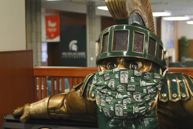 A face mask on the Sparty statue inside the the Michigan State University Student Union is seen on Friday, Aug. 21, 2020. Students at Michigan universities are receiving emails from their schools welcoming them back for the fall, but a cloud of concern is hovering because of the coronavirus pandemic. To go online or to come in person has been the debate, but since Michigan State University announced Tuesday it will go online for the next semester, the debate is reaching a fever pitch. (AP Photo/Anna Nichols)