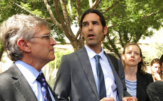 FILE - In this June 11, 2019, file photo, Scott Warren, center, speaks outside federal court, in Tucson, Ariz., after a mistrial was declared in the federal case against him. Warren is scheduled to testify Tuesday, Nov. 19, 2019, in the second criminal case against his actions as a member of a humanitarian aid group. Prosecutors say Warren was arrested in early 2018 after harboring two men who sneaked across the U.S.-Mexico border. (AP Photo/Astrid Galvan, File)