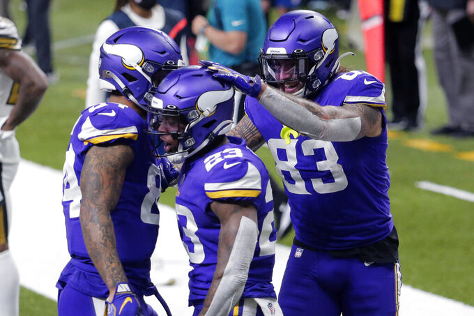 Minnesota Vikings running back Mike Boone (23) celebrates his touchdown with tight end Tyler Conklin (83) and tight end Irv Smith (84) in the first half of an NFL football game in New Orleans, Friday, Dec. 25, 2020. (AP Photo/Brett Duke)