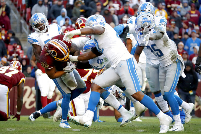 Washington Redskins running back Adrian Peterson, left, is stuffed by a host of Detroit Lions defenders during the second half of an NFL football game, Sunday, Nov. 24, 2019, in Landover, Md. (AP Photo/Alex Brandon)