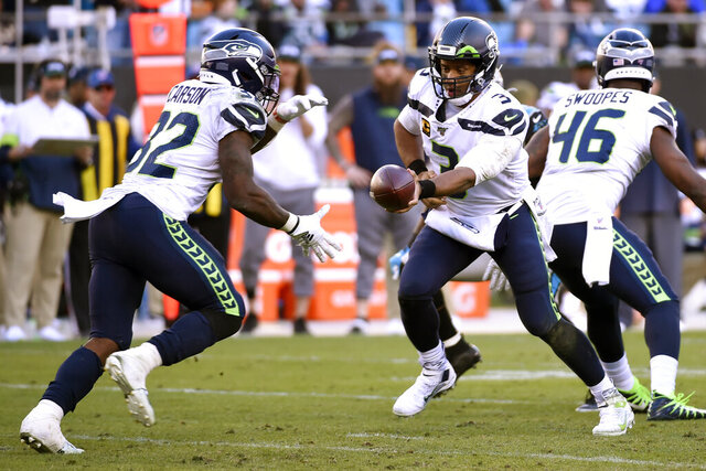 Seattle Seahawks quarterback Russell Wilson (3) hands pff to running back Chris Carson (32) during the second half of an NFL football game against the Carolina Panthers in Charlotte, N.C., Sunday, Dec. 15, 2019. (AP Photo/Mike McCarn)