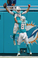 Miami Dolphins tight end Durham Smythe (81) lifts tight end Mike Gesicki (88) after Gesicki scored a touchdown, during the second half of an NFL football game against the Cincinnati Bengals, Sunday, Dec. 6, 2020, in Miami Gardens, Fla. (AP Photo/Lynne Sladky)