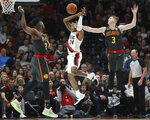 Portland Trail Blazers guard Kent Bazemore, center, is fouled by Atlanta Hawks guard Kevin Huerter, right, as forward Bruno Fernando defends during the first half of an NBA basketball game in Portland, Ore., Sunday, Nov. 10, 2019. (AP Photo/Craig Mitchelldyer)